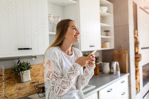 Young woman using her smartphone at home