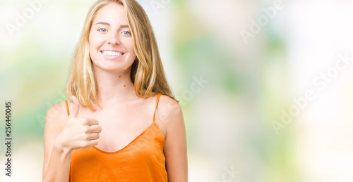 Leinwanddruck Bild Beautiful young woman wearing orange shirt over isolated background doing happy thumbs up gesture with hand. Approving expression looking at the camera showing success.