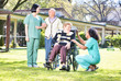 Group of aged senior people and multi ethnic nurses on the garden talking and smiling