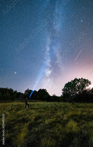 Astrofotografia con una persona iluminando hacia el infinito entre arboles y montañas © Roberto