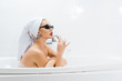 Leinwanddruck Bild - beautiful woman in white towel and sunglasses taking bath and drinking beverage