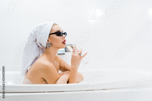 Leinwanddruck Bild beautiful woman in white towel and sunglasses taking bath and drinking beverage