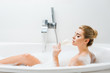 Leinwanddruck Bild - attractive woman taking bath and drinking beverage from champagne glass in bathroom