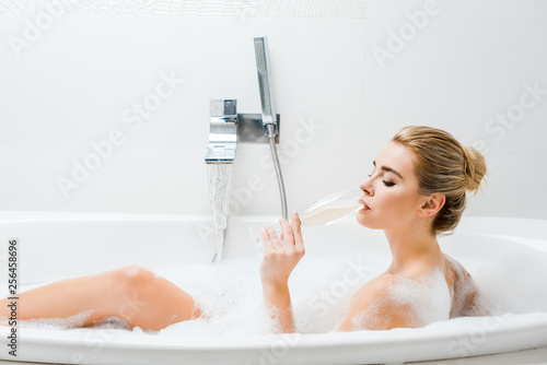 Leinwanddruck Bild attractive woman taking bath and drinking beverage from champagne glass in bathroom