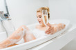 Leinwanddruck Bild - selective focus of champagne glass holding by beautiful and blonde woman in bathroom