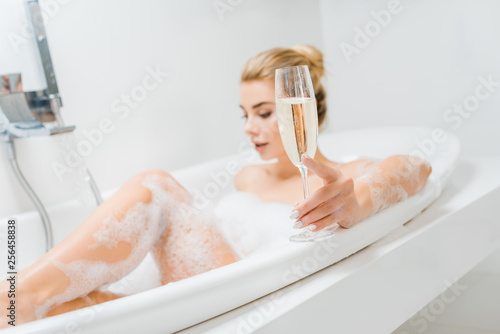 Leinwanddruck Bild selective focus of champagne glass holding by beautiful and blonde woman in bathroom