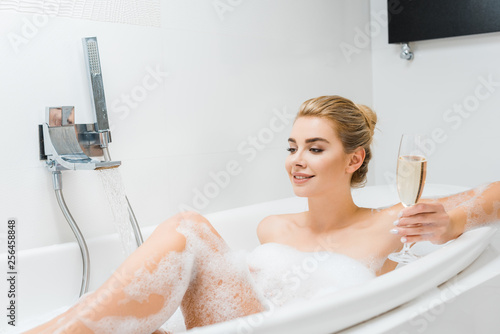 Leinwanddruck Bild beautiful and smiling woman taking bath and holding champagne glass in bathroom