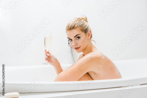 Leinwanddruck Bild beautiful and blonde woman taking bath and holding champagne glass in bathroom
