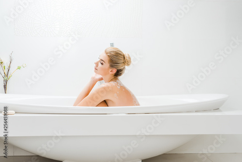 Leinwanddruck Bild side view of beautiful and blonde woman taking bath with foam in bathroom