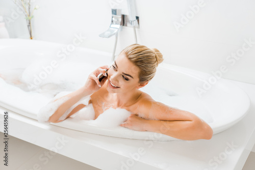 Leinwanddruck Bild attractive and smiling woman taking bath with foam and talking on smartphone in bathroom