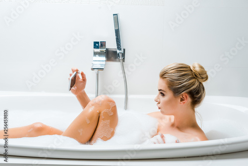 Leinwanddruck Bild side view of attractive and blonde woman taking bath with foam and taking selfie in bathroom