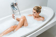 Leinwanddruck Bild - attractive and blonde woman taking bath with foam and taking selfie in bathroom