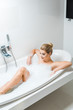 Leinwanddruck Bild - attractive and smiling woman taking bath with foam in bathroom