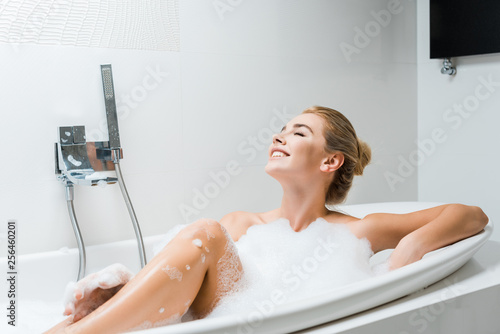 Leinwanddruck Bild attractive, blonde and smiling woman taking bath with foam in bathroom