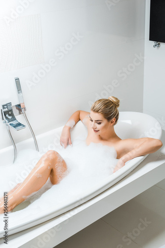 Leinwanddruck Bild attractive and smiling woman taking bath with foam in bathroom