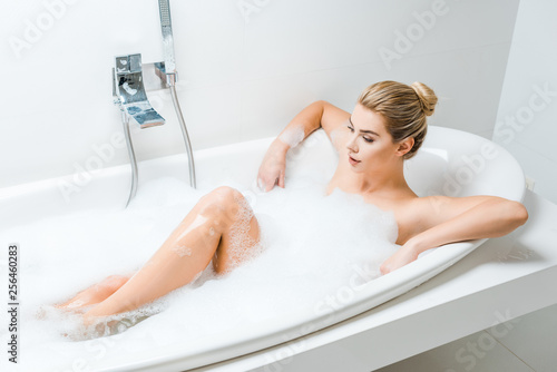 Leinwanddruck Bild attractive and blonde woman taking bath with foam and looking away in bathroom