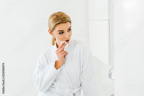 Leinwanddruck Bild beautiful and blonde woman in white bathrobe using cotton pad and looking away