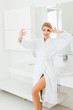 Leinwanddruck Bild - beautiful and smiling woman in white bathrobe with eye patches on face taking selfie