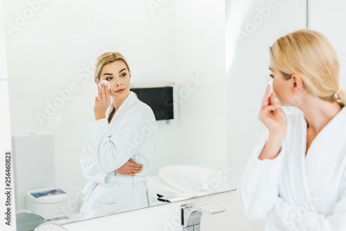 Leinwanddruck Bild selective focus of beautiful and blonde woman in white bathrobe using cotton pad and looking at mirror