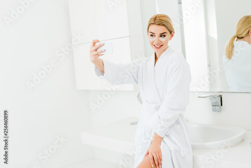 Leinwanddruck Bild beautiful and smiling woman in white bathrobe with eye patches on face taking selfie in bathroom