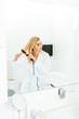 Leinwanddruck Bild - beautiful and blonde woman in white bathrobe using flat iron in bathroom