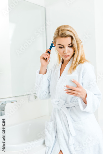 Leinwanddruck Bild beautiful and blonde woman holding comb and using smartphone in bathroom