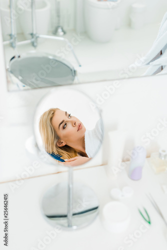 Leinwanddruck Bild selective focus of beautiful and blonde woman holding comb and looking away in bathroom