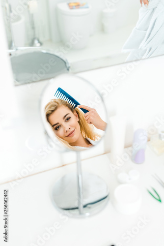 Leinwanddruck Bild selective focus of beautiful and smiling woman holding comb and looking at mirror