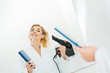 Leinwanddruck Bild - selective focus of beautiful and smiling woman in white bathrobe holding hairdryer and comb