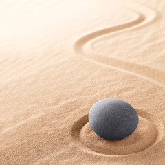 Spa wellness for inner life therapy and spiritual health. Zen meditation stone for relaxation. Concept for purity balance and harmony. Background with raked sand. © kikkerdirk