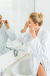 Leinwanddruck Bild - selective focus of attractive and blonde woman in white bathrobe brushing teeth with dental floss