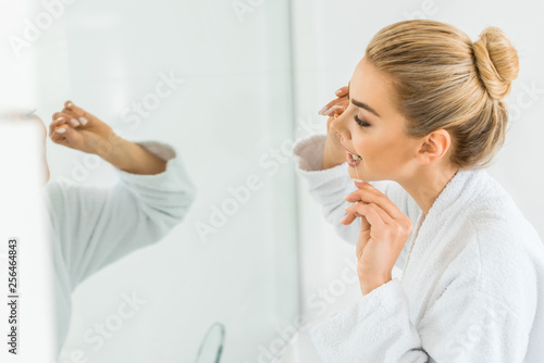 Leinwanddruck Bild selective focus of attractive and blonde woman in white bathrobe brushing teeth with dental floss