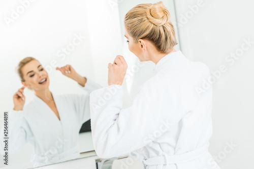 Leinwanddruck Bild selective focus of beautiful and blonde woman in white bathrobe brushing teeth with dental floss