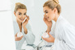 Leinwanddruck Bild - selective focus of attractive and blonde woman in white bathrobe applying face cream and looking at mirror