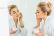 Leinwanddruck Bild - selective focus of attractive and smiling woman in white bathrobe applying face cream in bathroom