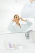 Leinwanddruck Bild - selective focus of attractive woman in white bathrobe applying face cream in bathroom