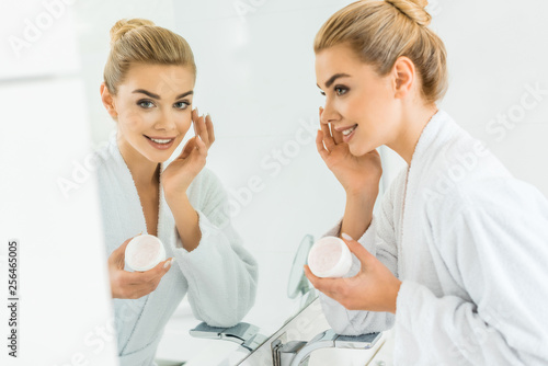 Leinwanddruck Bild selective focus of attractive and blonde woman in white bathrobe applying face cream and looking at mirror