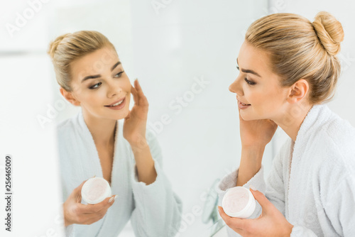 Leinwanddruck Bild selective focus of attractive and smiling woman in white bathrobe applying face cream in bathroom