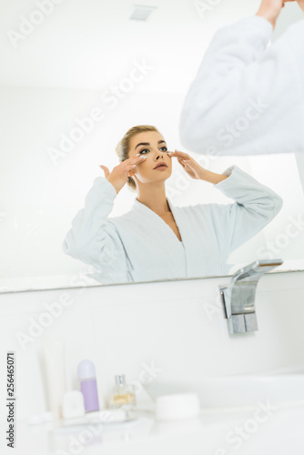 Leinwanddruck Bild selective focus of attractive woman in white bathrobe applying face cream in bathroom