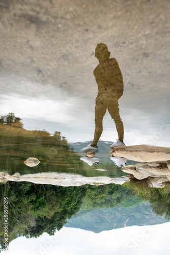 Leinwanddruck Bild Invisible man in white sneakers reflected on water surface