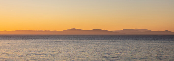 Aegean sea and Attica Greece hills, view from Kea island at sunset time, clear sky background, banner