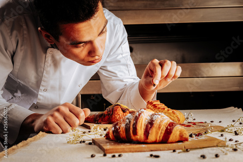 Talented professional baker finishing decoration of pastry desserts