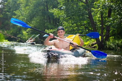 Foto Murales Friends swim in kayaks on a river rafting. Funny guys in boat rowing oars in canoe