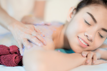 Young Asian woman receiving salt massage in spa salon, Hand putting salt scrub on female back, Spa concept © ake1150