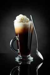 Layered coffee cocktail with whipped cream.