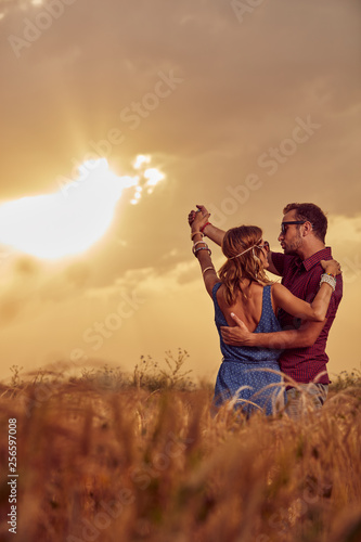 Couple in sunset / sunrise time in a wheat field.
