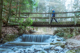Male hiker walking on bridge over a fairy tale creek