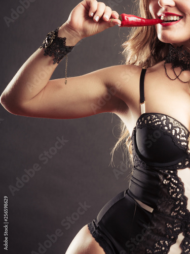 Woman wearing sexy lingerie holding chilli pepper - 256598629