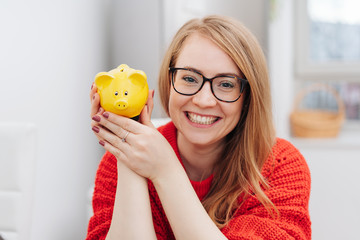 Happy young woman holding a yellow piggy bank © contrastwerkstatt
