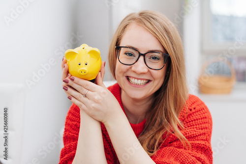 Happy young woman holding a yellow piggy bank - 256600840